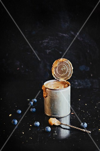 A tin of dulce de leche and blueberries