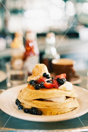 Pancakes with blueberries, strawberries, maple syrup and butter (USA)