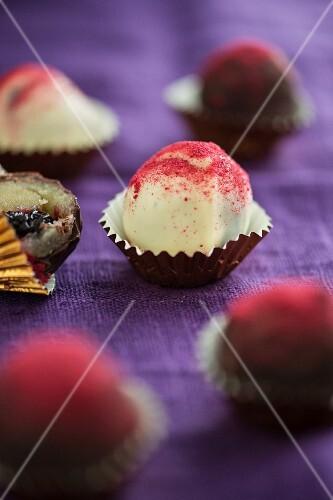 Cherry-marzipan bites with dark and white chocolate glaze and cherry powder