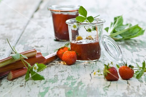 Jars of strawberry and rhubarb jam, fresh strawberries, rhubarb and strawberry flowers on a wooden table