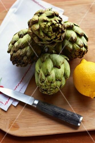 Artichokes, a lemon and a knife on a chopping board
