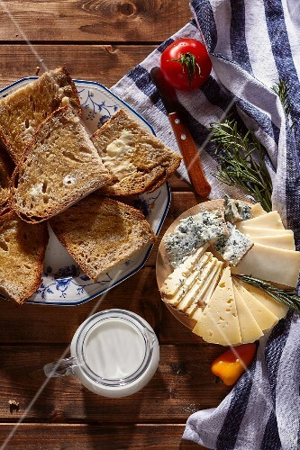 A cheese platter, toast and milk (seen from above)