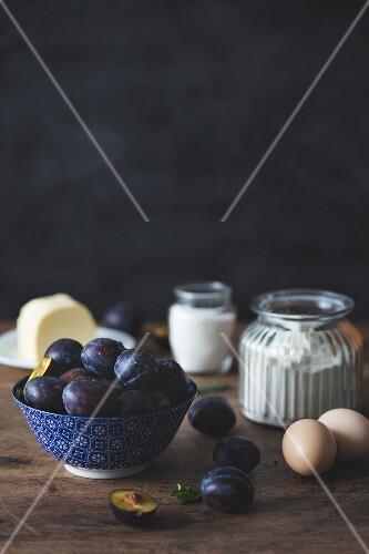 Various cake ingredients (fresh plums, flour, eggs, sugar, butter)