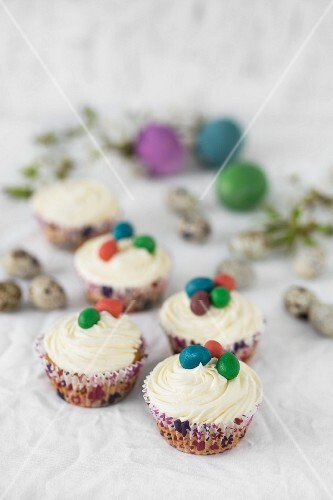 Easter cupcakes with white frosting and colourful marzipan eggs