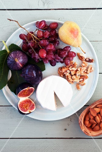 Brie with figs, grapes, pears and walnuts on a plate