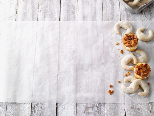 Caramelised almond cupcakes and vanilla crescent biscuits on baking paper