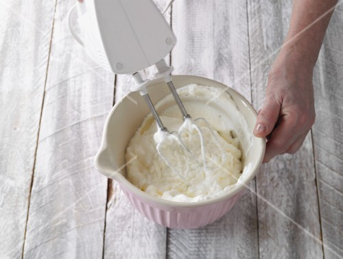 Cream being whipped with a hand whisk