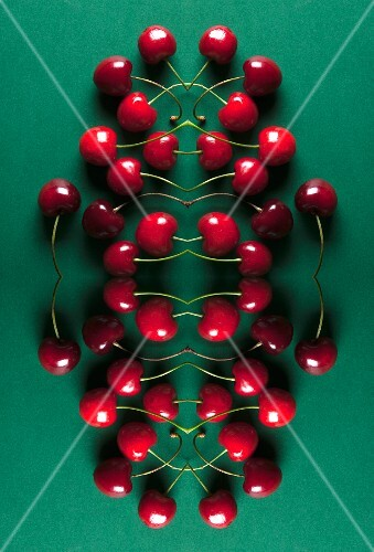 A digital composition of mirrored images of cherries