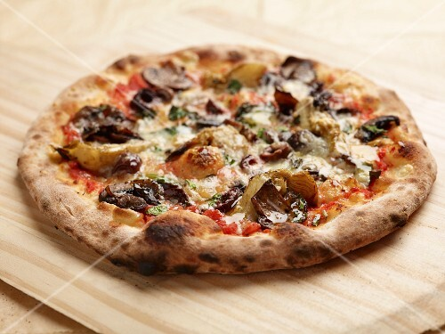 A four seasons pizza baked in a wood-fired oven topped with mushrooms, artichokes and olives