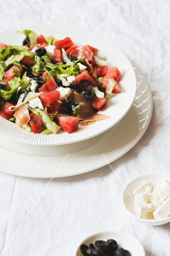 A summer salad with watermelons, olives, feta cheese and prosciutto