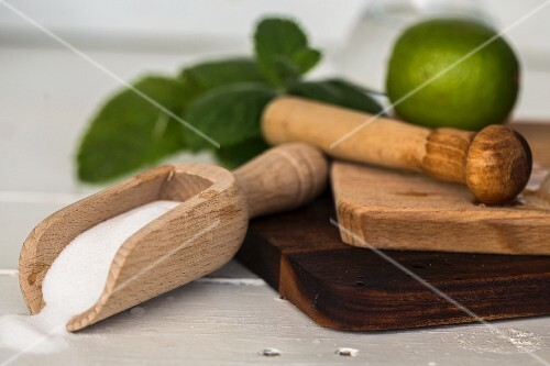 A muddler, limes, a wooden scoop with sugar on a wooden board