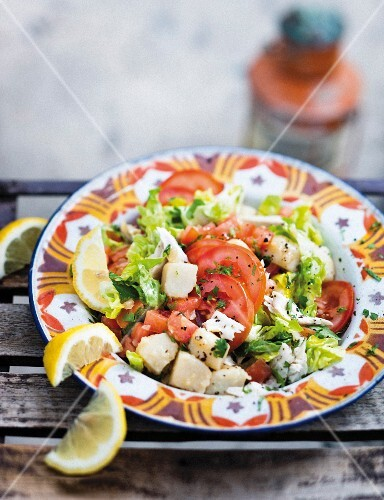 Warm fish and potato salad with tomatoes, lemons and coriander