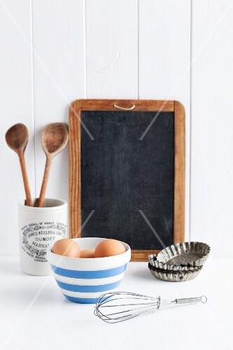 Eggs, a whisk, baking tins, wooden spoons and a blackboard