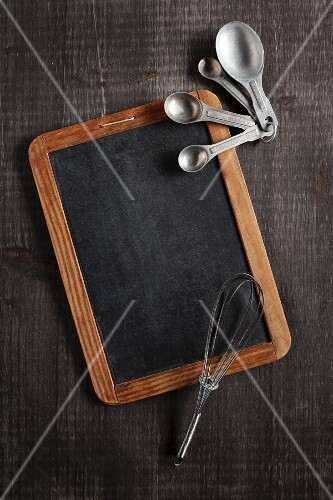 An old chalkboard, measuring spoons and a whisk on a dark brown wooden surface
