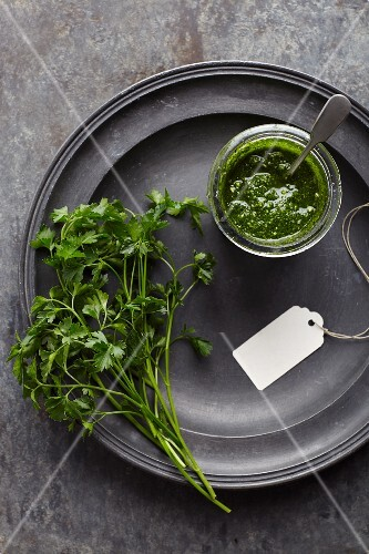 Parsley pesto in a jar on pewter plate