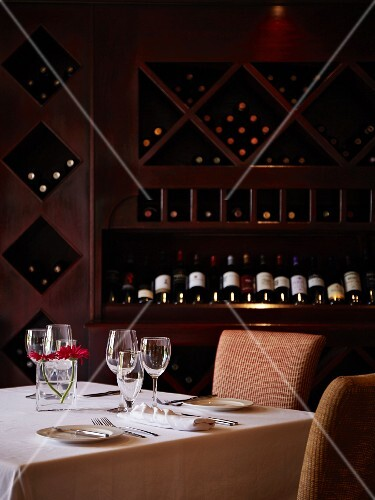 A table laid for two in front of a wine shelf in a restaurant