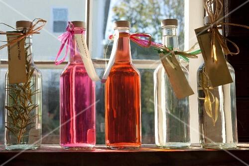 Homemade flavoured vinegar in bottles on a window sill