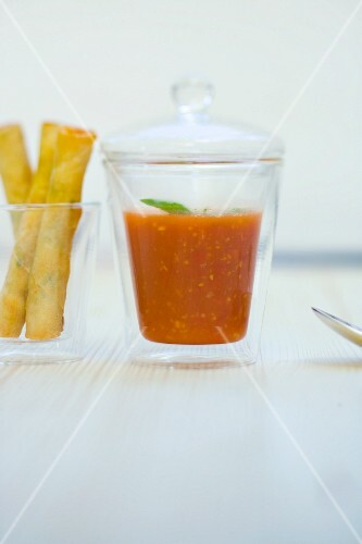 Tomato and ginger soup in a glass with crispy prawn rolls