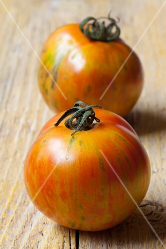 Two tomatoes on a wooden table