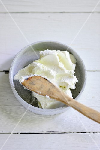 A bowl of cream cheese with a wooden spoon