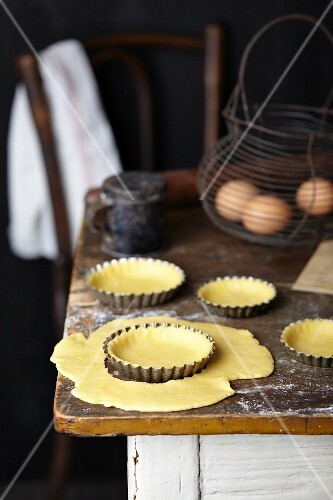 Shortcrust pastry for apple and frangipane tart in tart tins on a rustic kitchen table