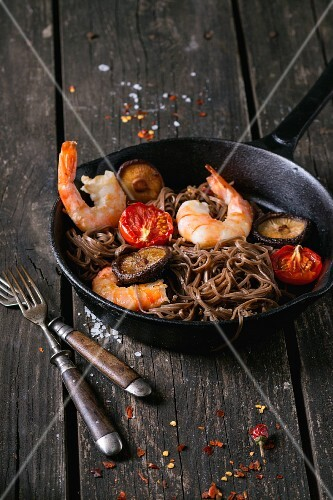 Prawns with soba noodles, mushrooms and tomatoes in a pan