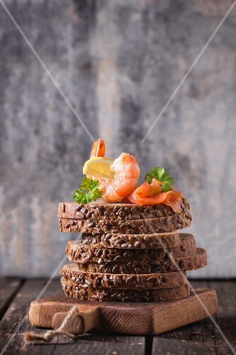 A stack of wholemeal bread slices topped with prawns and smoked salmon