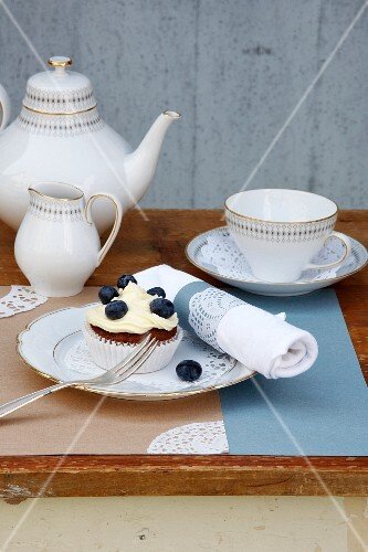 Coffee and cake on outdoor table decorated with vintage-style lace doilies