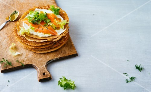 A stack of buckwheat pancakes with cream cheese and smoked salmon