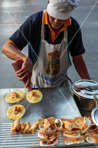 A man making Thai rice flour crêpes