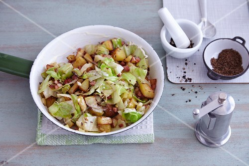 Quick fried potatoes with white cabbage and bacon