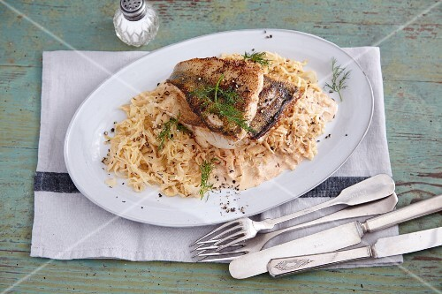 Fried fish fillets on a bed of sauerkraut