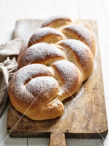 Vegan yeast dough with icing sugar on a chopping board