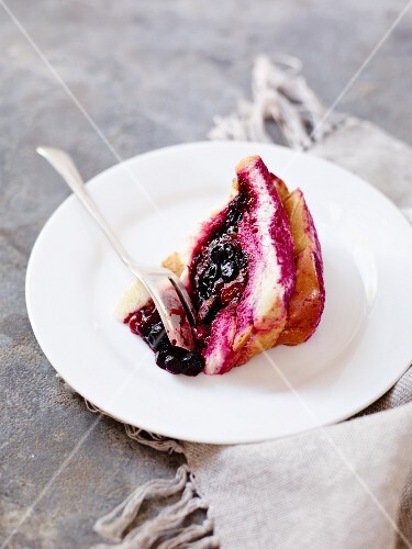 A slice of berry cake on a plate with a fork