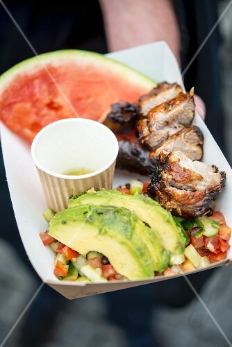 A hand holding grilled pork with a vegetable salad, avocado and melon in a paper dish