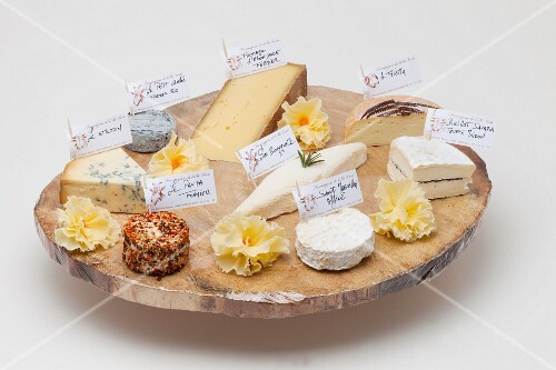Various types of cheese on a rustic wooden platter