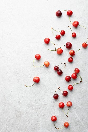 Fresh cherries on a white surface (seen from above)