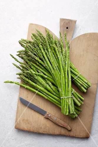 Bundles of green asparagus on a wooden chopping board (seen from above)