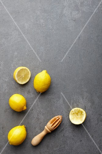 Lemons, whole and halved, with a wooden lemon squeezer (seen from above)