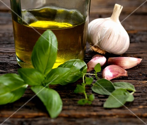 Ingredients for a salad dressing with olive oil, garlic, oregano, thyme and basil