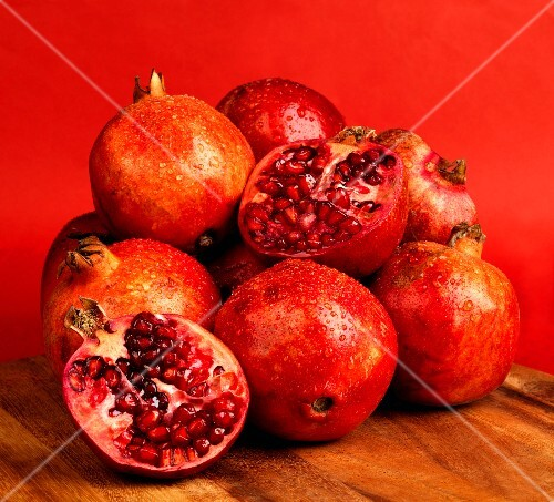 Pomegranates and two pomegranate halves against a red background