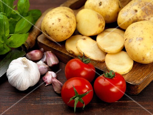 An arrangement of potatoes, tomatoes, garlic and basil
