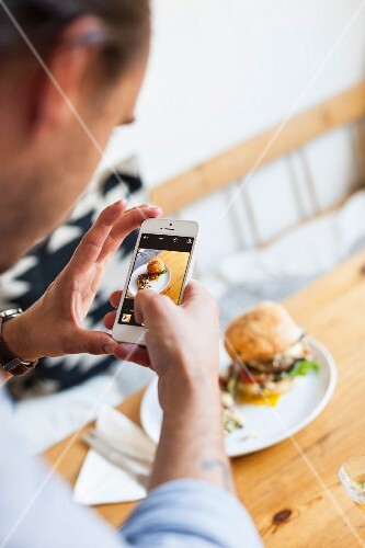 A man taking a photo of a burger with a smart phone