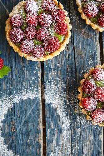 Mini raspberry and matcha tartlets dusted with icing sugar