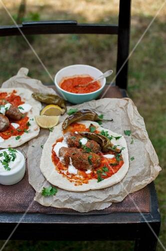 Cevapcici, on unleavened bread with ajvar, yoghurt, fresh parsley, roasted green chillis and lemon wedges