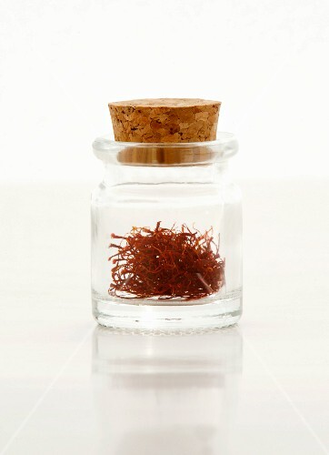 Saffron threads in a glass bottle with a cork on a white surface