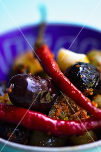 Marinated chillis with olives in a blue bowl