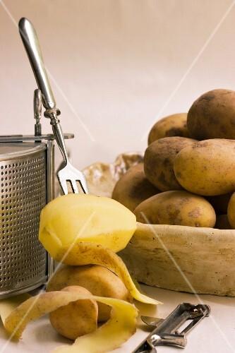Boiled potatoes and a half peeled potato on a fork