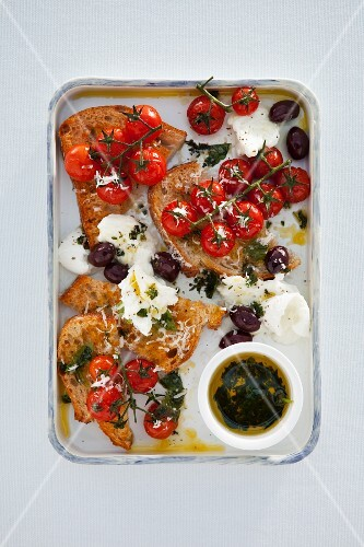 Bread salad with baked cherry tomatoes, olives and mozzarella