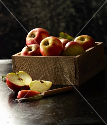 Red apples in a wooden crate with a sliced apple and a knife in the foreground